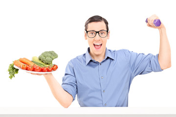 Man holding plate with vegetables and a dumbbell
