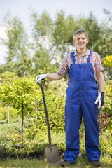 Full-length portrait of confident gardener holding spade in plant nursery