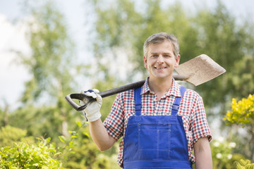 Portrait of happy man carrying spade on shoulder in plant nursery