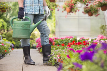 Low section of man holding watering can at greenhouse