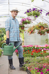 Full-length portrait of smiling man carrying watering can in greenhouse
