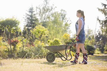 Full-length side view of female gardener pushing wheelbarrow at plant nursery