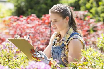 Female supervisor writing on clipboard in garden