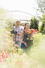 Gardeners holding potted plants outside greenhouse