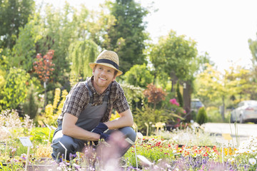 Man looking away while gardening at plant nursery