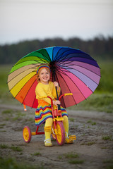 little cute girl on the bicycle with umbrella in her hands