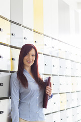 Portrait of beautiful businesswoman holding file in locker room at creative office