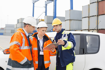 Workers discussing over clipboard beside car in shipping yard