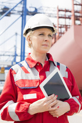 Female engineer holding tablet computer in shipping yard