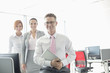 Portrait of happy businessman holding tablet PC with female colleagues in background at office