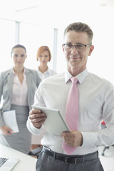 Portrait of happy businessman holding digital tablet with female colleagues in background at office