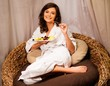 Woman relaxing in comfortable chair with plate of fruits