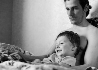 father and son relaxing in bed, reading book