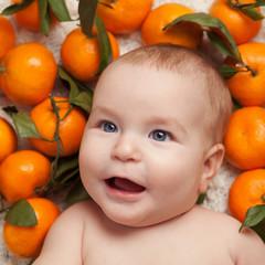 Portrait of newborn happy baby with mandarin