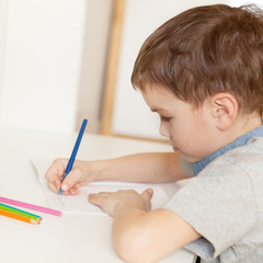 Serious pensive pupil sits at desk