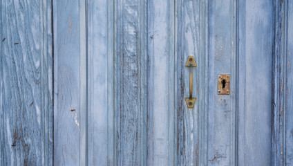 Old blue run-down wooden door and lock
