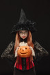 Girl with Halloween pumpkin on black background - 74590240