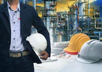 engineering man standing with white safety helmet against  oil r