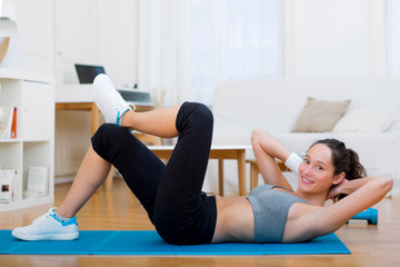 Young attractive girl doing exercise at home