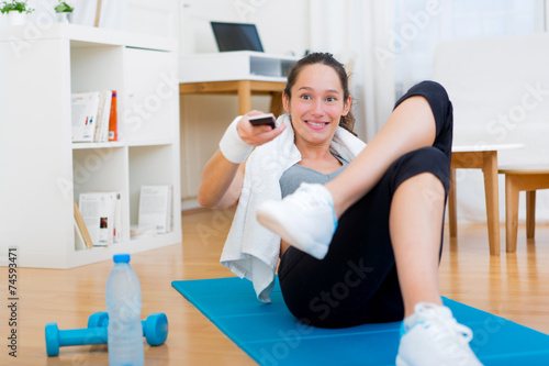 canvas print picture Young attractive woman watching sport exercises on tv