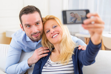 Young attractive couple having fun doing selfie