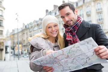 Couple of young attractive tourist watching map