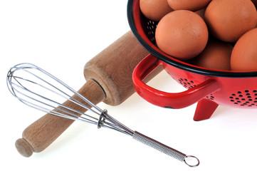 Fouet, rouleau à pâtisserie et œufs dans une passoire
