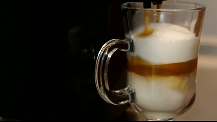 coffee machine pouring coffee trickle into the glass. Latte