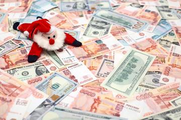 Toy Santa lying down on money background