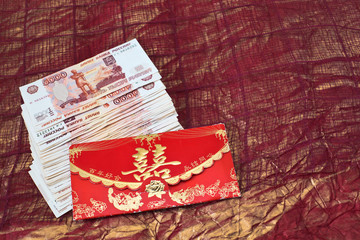 Chinese money envelope & stack of russian rubles