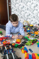 Teenage boy playing with toy cars in  room