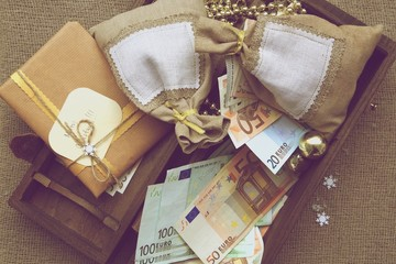 Wooden box full of Christmas presents and euros