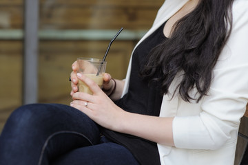 Young woman holding glass with ice coffee