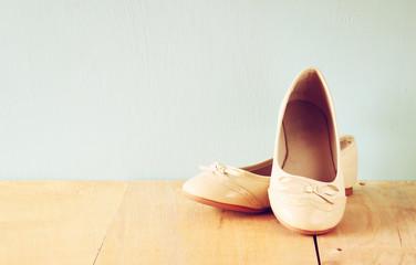 girl shoes over wooden deck floor. filtered image