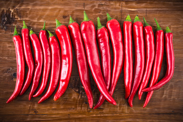 Red hot chili peppers on rustic wood background.