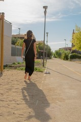 Girl with black dress walking towards her shoes on sand