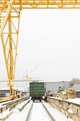 gantry crane over railway carriage in outdoor warehouse
