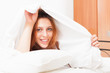 Red-haired woman waking up on white sheet in bed at home