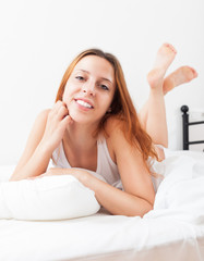 Smiling long-haired woman lying on white sheet in bed at home