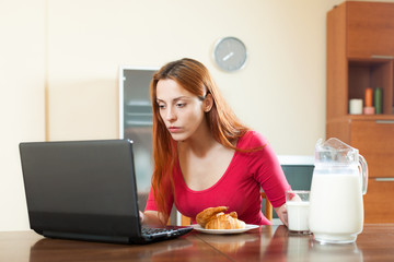 Young woman having breakfast checking e-mails on laptop in morni