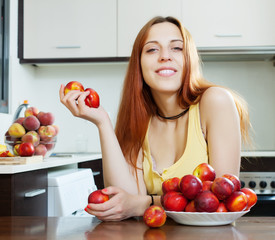 Happy  woman holding nectarines