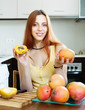 Positive  woman with ripe mango in home