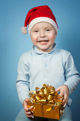 Boy in a cap of Santa Claus with gifts