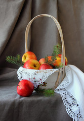 Still life with a basket of apples on white napkin.