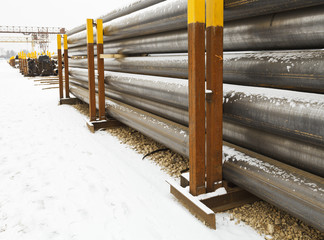 stacks of construction pipes on outdoor warehouse
