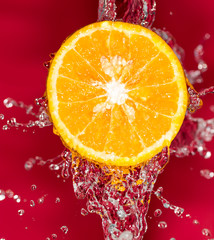orange in water on a red background background