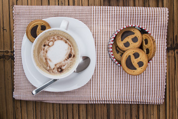 Cup of cafe au lait with smiling cookies