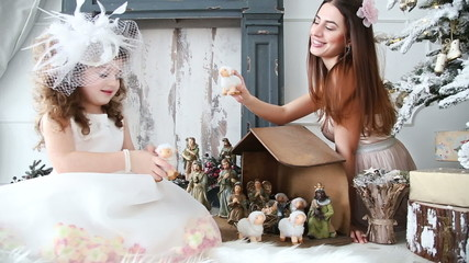 Mom and daughter play in the birth of Jesus - dolly shot