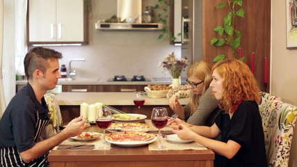 Group of happy friends eating pizza in dining room at home.