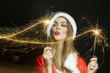 beautiful woman in Santa outfit with New year party sparklers